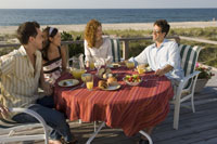 Two couples eating on deck next to beach