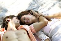 Hispanic couple laying together on beach