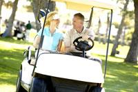 Couple driving golf cart