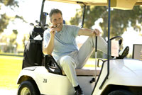 Man relaxing with cigar in golf cart