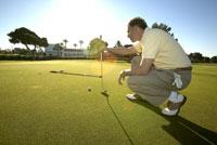 Male golfer lining up shot 11029010055| 写真素材・ストックフォト・画像・イラスト素材|アマナイメージズ