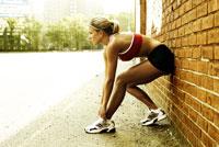 Woman runner stretching against wall 11029010104| 写真素材・ストックフォト・画像・イラスト素材|アマナイメージズ