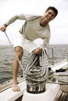 Young man adjusting rigging on sailboat