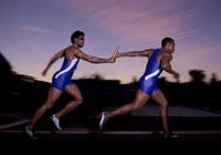 Male athletes passing the baton