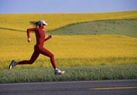 Woman jogging on rural road 11029010278| 写真素材・ストックフォト・画像・イラスト素材|アマナイメージズ