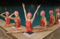 Synchronized swim team by swimming pool