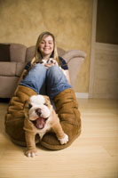 Teenage girl playing with bulldog