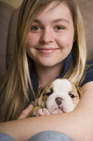 Teenage girl holding puppy