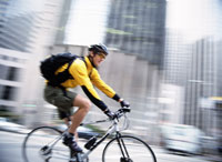Blurred view of man biking downtown