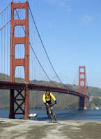 Man biking by bridge