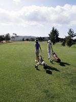 Women pulling golf carts on fairway