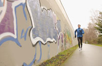 Man running with graffiti in background