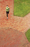Woman running on brick sidewalk 11029010823| 写真素材・ストックフォト・画像・イラスト素材|アマナイメージズ