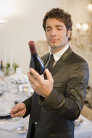 Man examining bottle of wine