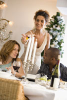 Woman lighting candles at dinner table