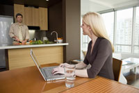 Man cooking as wife uses laptop at table