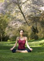 Woman meditating outdoors 11029012237| 写真素材・ストックフォト・画像・イラスト素材|アマナイメージズ
