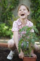 Girl planting tomato plant 11029012407| 写真素材・ストックフォト・画像・イラスト素材|アマナイメージズ
