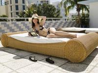 Woman sunbathing on wicker bed 11029012430| 写真素材・ストックフォト・画像・イラスト素材|アマナイメージズ