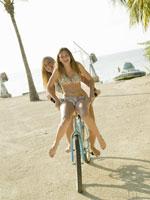 girls in bikinis riding a bike on beach