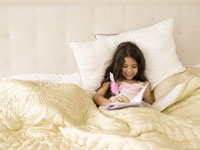 Girl writing in diary in bed