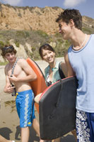 Teenagers carrying body boards on beach