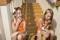 Twin girls eating apples 11029012714| 写真素材・ストックフォト・画像・イラスト素材|アマナイメージズ