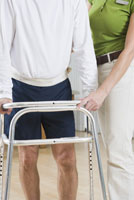Physical therapist helping man walk