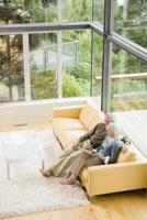 couple reading on sofa 11029012967| 写真素材・ストックフォト・画像・イラスト素材|アマナイメージズ