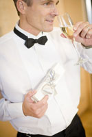 Man in tuxedo holding gift