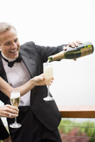Man pouring champagne for wife