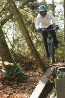Boy riding mountain bike on rocks 11029013053| 写真素材・ストックフォト・画像・イラスト素材|アマナイメージズ