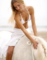 woman riding a horse at beach
