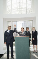 people with arms raised at podium