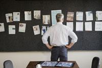 man looking at wall of articles