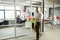 man walking past office
