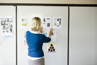 woman hanging paperwork on wall