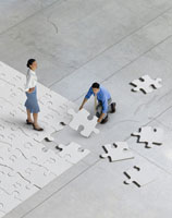people putting together jigsaw puzzle