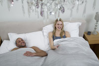 Couple watching television in bed