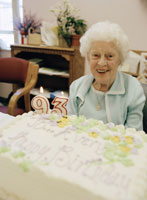 Elderly adult woman with birthday cake