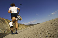 Couple jogging on craggy track