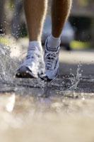 Man jogging through puddle