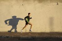 Man jogging on urban sidewalk 11029013777| 写真素材・ストックフォト・画像・イラスト素材|アマナイメージズ