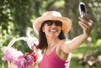Woman photographing herself 11029013843| 写真素材・ストックフォト・画像・イラスト素材|アマナイメージズ