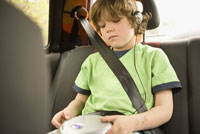 boy listening to headphones in backseat