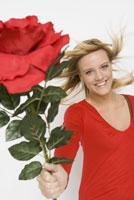 Woman holding out oversized flower 11029014055| 写真素材・ストックフォト・画像・イラスト素材|アマナイメージズ