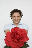 Man holding out oversized flower 11029014058| 写真素材・ストックフォト・画像・イラスト素材|アマナイメージズ