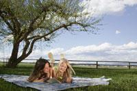 girls lying on blanket outdoors