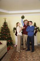 man holding mistletoe for husband