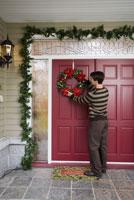 Man hanging Christmas wreath